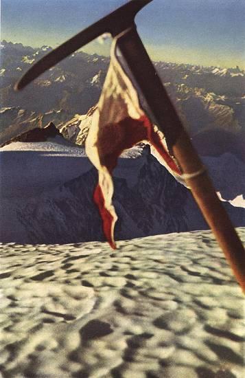 """Η φωτογραφία-πειστήριο που τράβηξε ο Hermann Buhl στην κορυφή, το απόγευμα της 3ης Ιουλίου. Πίσω απ το τυρολέζικο σημαιάκι που είναι δεμένο στο πιολέ, διακρίνεται η """"Ασημένια Σέλλα"""" (το επίπεδο σημείο που φωτίζεται από τον ήλιο, στο κέντρο αριστερά) και στο βάθος η """"θάλασσα"""" των κορυφών του Καρακορούμ."""