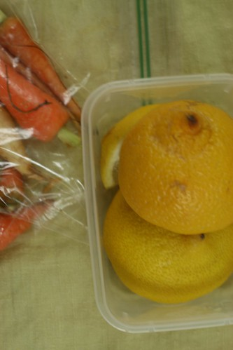 A close up of two half lemons and a lemon wedge in a plastic container. To their left is a baggie of carrots.