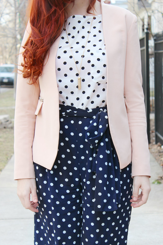 Contrasting navy and white polka dot jumpsuit with a rose quartz/blush pink blazer.