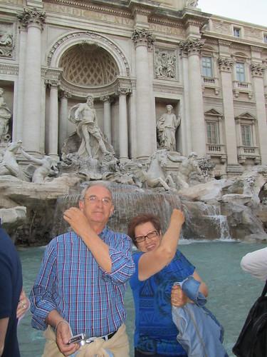 Tirando las monedas en la Fontana di Trevi en Roma