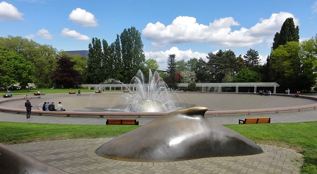 Image shows the back of a bronze whale, surrounded by brick. Behind it is a green stretch of lawn, and then the International Fountain, which is a huge silver ball shooting out several curving jets of water within a huge shallow bowl.