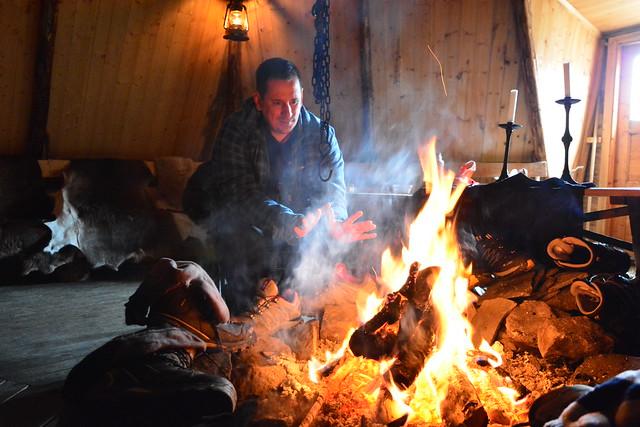 Sele calentándose las manos en un lavvu sami