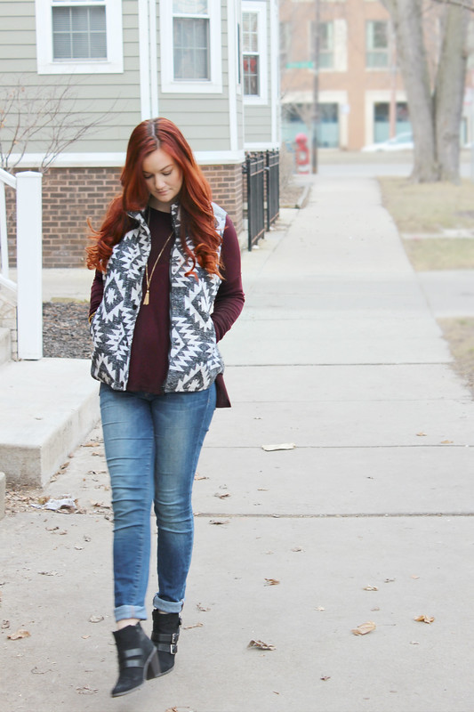 Full outfit shot with street in the background. Wearing a black and white southwestern print puff vest over a long sleeve burgundy sweater. Bottoms are Joe's Jeans in a skinny cut with cuffed bottoms. Shoes are cute black and gold booties with a heel.