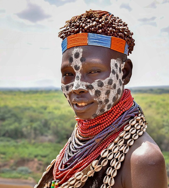Karo Woman in Ethiopia adorned with cowrie shells and glass beads