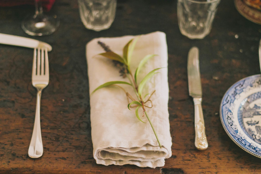 a single sprig of lavender on a cloth napkin, set with vintage cutlery and side plate