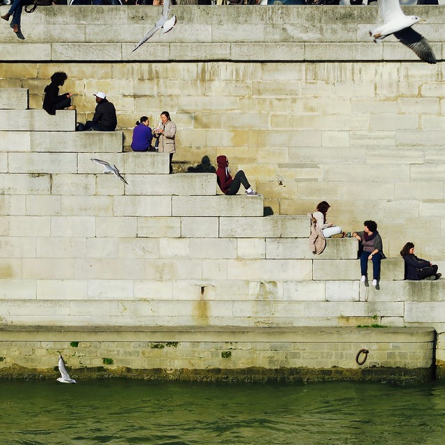 people sitting on the steps leading down to the Seine