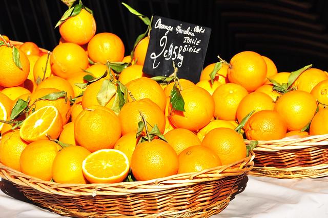 """Nizza/Nice, im März 2016. Auf dem """"Cours Saleya"""" in Nizza, ganz in der Nähe der wuseligen Altstadtgässchen, findet täglich der berühmte Marché aux fleurs (Blumenmarkt) statt. Natürlich gibt es nicht nur Blumen (zurzeit, im März, sind die Mimosen vorherrschend), sondern die bunten Stände bieten einfach alles, was man sich von einem provençalischen, mediterranen Markt erwartet und erhofft: Gemüse, Obst (vor allem Zitronen, Orangen, Mandarinen), Brot, Käse, Kräuter und Gewürze, Oliven, Fisch, Schönes aus Olivenholz, kleine Geschenke ... ja, sogar Maler stellen hier ihre Kunstwerke aus. Der beliebte Socca-Stand ist immer umlagert und überall riecht es appetitlich und ganz verführerisch. Ein Markttag in Nice: very nice, wie an einem der Stände mittels Wortspielerei versprochen wird."""