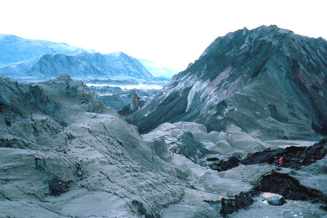 Image shows enormous mounds of rocky debris from the summit of Mount St. Helens, dusted in gray ash. To the left, there is a light brownish-gray pile of dirt and rock in the shape of a low ridge. To the center right, there is a huge mound of darker gray debris with a ragged white strip in the center. Parts of the valley are visible in the background, with the ridges bounding the Toutle River valley beyond. In the right foreground, a tiny human in a red coat is walking on the debris flow near short black cliffs.