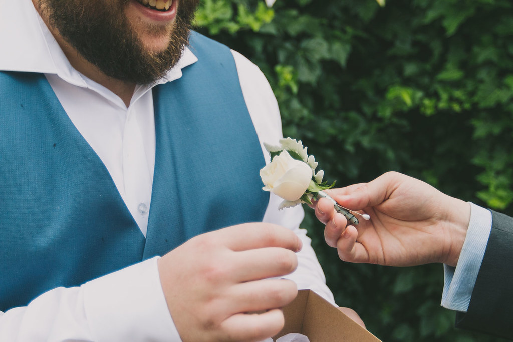 bb getting his buttonhole flower arrangement pinned in place