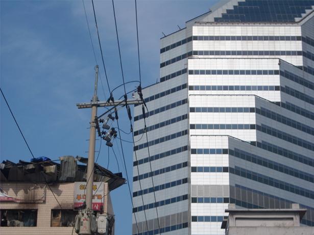圖四:《轉型成為全球都市》。遭到祝融的鷹架殘骸在一棟被清空的建築物屋頂上,鎮暴警察與抗議者在上頭對峙,國際大廈在一旁成為直接的背景。(攝影:Cheon Malsun)