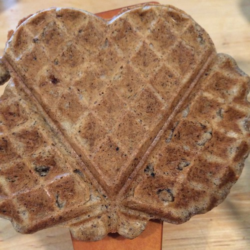 A close up of a heart-shaped waffle, with a couple blobs of waffle that didn't manage to become heart-shaped on each side.