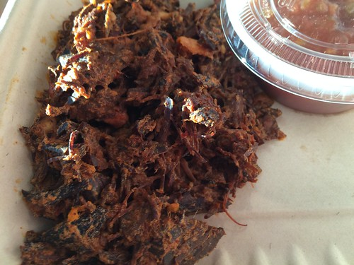 A close up of brisket in a to-go container.