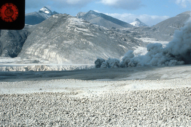 Image shows a pale gray, nearly flat expanse of rocks and ash in the foreground. Beyond it, a gully can be seen just before bare ridges and mountains rise, dusted with gray ash and white snow. From the right, a pyroclastic flow is rolling across the pumice plain in the middle of the photo.