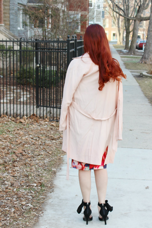 Outfit details from behind. Blush pink trench coat draped over my shoulders. Black heels with bows on the side.