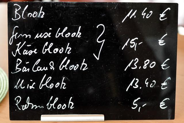 """1974 war ich erstmals mit meinen Eltern in Urlaub im Hohenlohischen. Damals haben wir dort den Blootz kennen gelernt, einen leckeren flachen Brotkuchen aus dem Holzofen. Der Name """"Blootz"""" ist ein Dialektwort für """"Platz"""". """"Platz"""" kommt wiederum von lateinisch """"placenta"""", was Kuchen bedeutet. Meist wird heute nur noch der Diminutiv von """"Platz"""" verwendet: das Plätzchen, z. B. in Form von Weihnachtsplätzchen. Der """"Platz"""" bzw. hohenlohische """"Blootz"""" ist die größere Ausgabe eines flachen Gebäckstücks aus Brotteig. Es gibt ihn pikant oder süß. Nur sehr behelfsmäßig kann man ihn UNGEFÄHR mit einer Pizza oder einem Flammkuchen vergleichen. Aber damit kommt man nicht so recht hin, Blootz ist eben Blootz und unvergleichlich. Es ist ein Kuchen, der früher beim wöchentlichen Brotbacken so nebenbei angefallen ist. Wenn der Ofen nach dem letzten Brot noch heiß war, hat man ihn mit flach ausgewalzten Stücken aus Brotteig befüllt, um die Hitze auszunutzen. Die Fladen wurden je nach Wunsch belegt, mit dem, was Haus und Hof so hergab. Zuerst eine Schicht Sauerrahm (Schmand), darauf unterschiedliche Beläge wie Zwiebeln, Gemüse, Speck …  Ursprünglich ein Arme-Leute-Essen, hat sich das Blootz-Essen zu einem beliebten Event gemausert. Nur noch wenige Gasthäuser bieten ihn an und wenn, dann meist nur einmal pro Woche, denn es ist viel Vorbereitungsarbeit nötig. Trotzdem ist der Blootz fast eine hohenlohische Nationalspeise zu nennen. Wo diese Köstlichkeit angeboten wird, ist die Gaststube proppenvoll; die Gäste kommen von weit angefahren. Wir sind sogar von Mannheim aus und hauptsächlich wegen des Blootz-Abends circa 200 Kilometer gefahren. Im Landgasthaus """"Zur Eiche"""" in Mainkling wird jeweils am Freitagabend Blootz angeboten. Außer der klassischen Variante gibt es dort auch vegetarische Versionen wie Gemüseblootz und Käseblootz, zurzeit ist Bärlauchblootz der große Renner. Serviert wird ganz rustikal auf großen, runden Holzbrettern. Mit mehreren Personen empfiehlt sich der Mix-Blootz: von"""