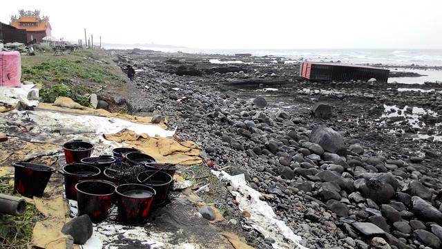 聖安宮前方,數個落海空櫃被海浪沖至岸邊。攝影:林倩如。