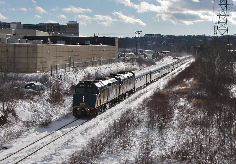 A shiny VIA train in the snow under sunny skies