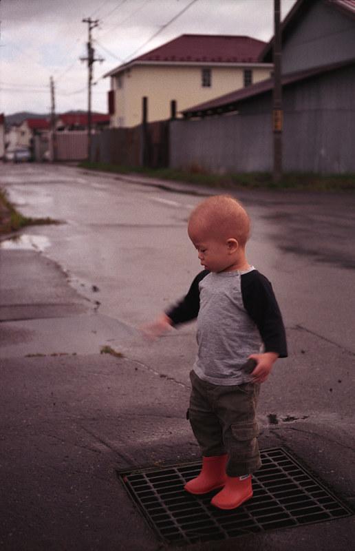 雨の日に石を投げる子