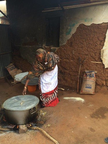 A parent volunteer using USDA-supplied corn-soy blend to prepare a nutritious porridge