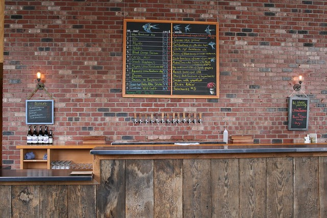 An empty bar, clean and very tidy. The taplist is centered over the taps which are, in turn, centered with regards to the bar. On either side there's a chalkboard listing something.