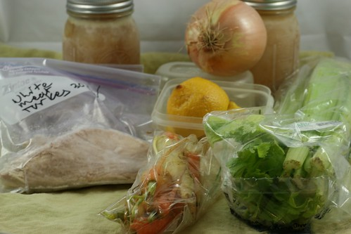 The ingredients for lemon-turkey soup. Two jars of homemade stock, celery, lemons, carrots, and turkey.