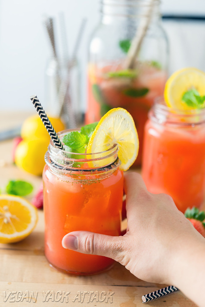 A couple of glasses of boozy mint strawberry lemonade next to a large jar of it, and a hand holding one