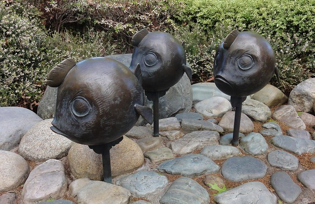 Image shows a set of round bronze fish on poles, in a staggered line. They have fins coming out of their foreheads that make them look like they have mohawks.