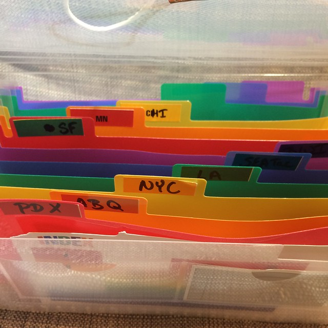 An open check organizer, labeled with several cities such as PDX, ABQ, NYC, and more.