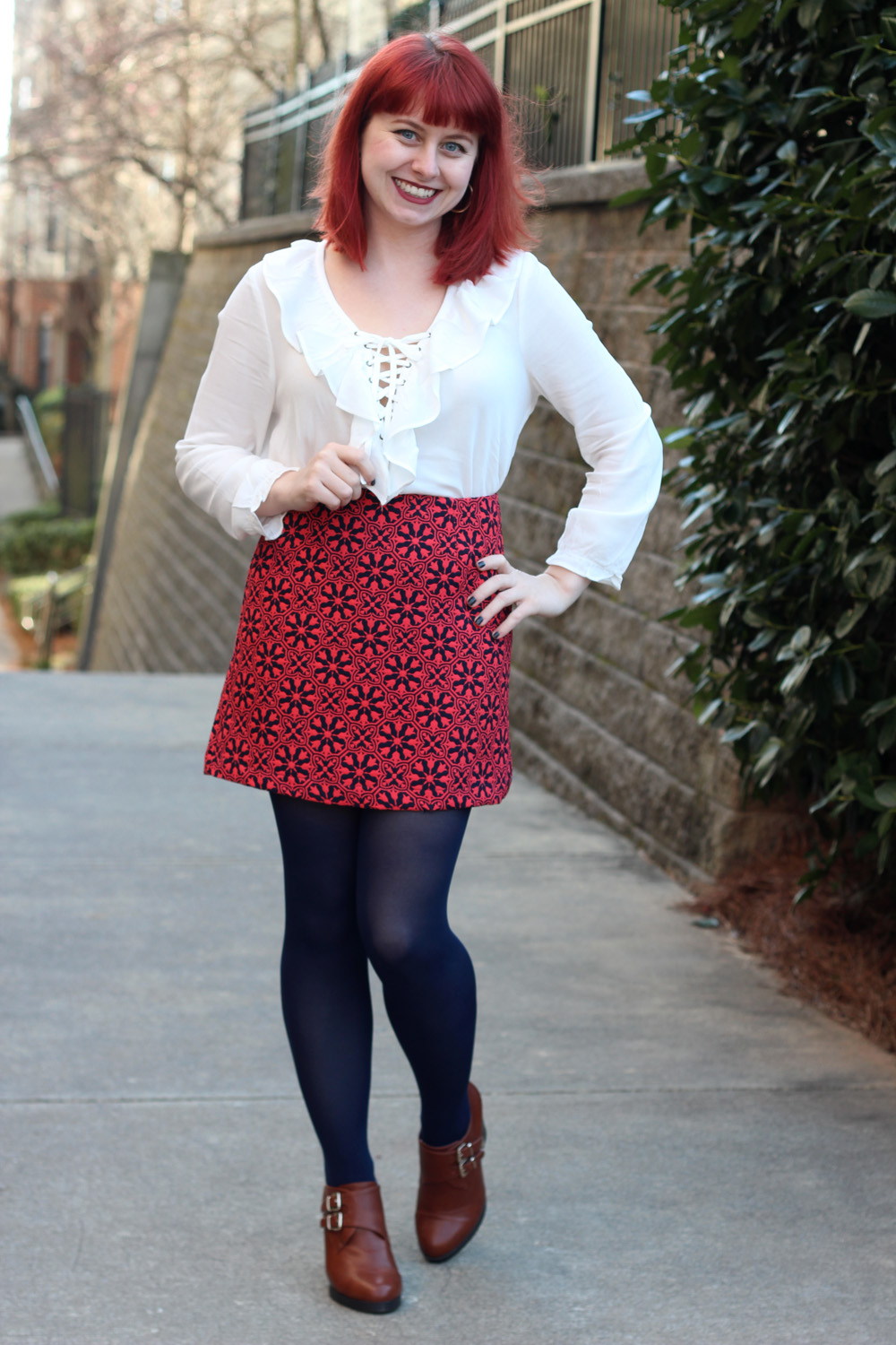 Retro Lace Up White Blouse with a Geometric Floral Mini Skirt, Navy Blue Tights, and Tall Tawny Brown Ankle Boots