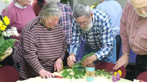 volunteers creating a flower arrangement.