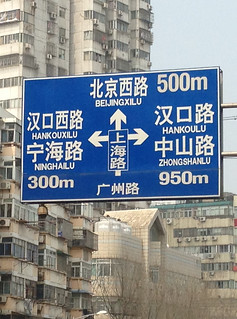 A street sign leading to five different destinations, in Chinese and English.