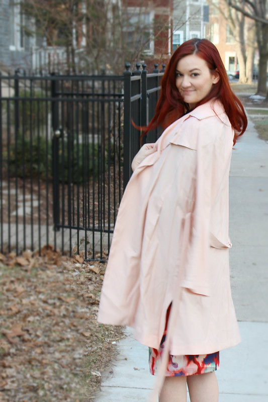 Looking over my shoulder with a blush pink trench coat draped over my shoulders.