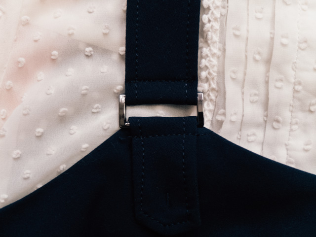 strap of navy pinafore dress