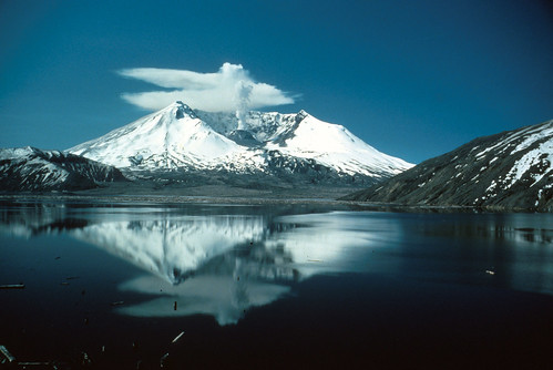 Image shows a snow-shrouded Mount St. Helens reflected in the calm waters of Spirit Lake. A plume of steam rises from the center of her crater: the top of it has been blown by the wind into anvil-shaped clouds close to the summit. The sky is a cloudless dark blue.