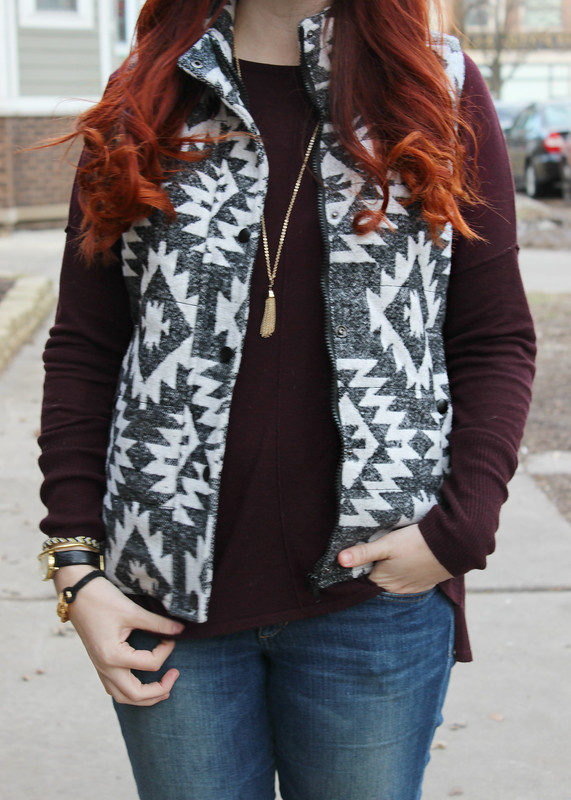 Close up of puffer vest and burgundy sweater. Also wearing a gold tassel necklace. Puffer vest has pockets.