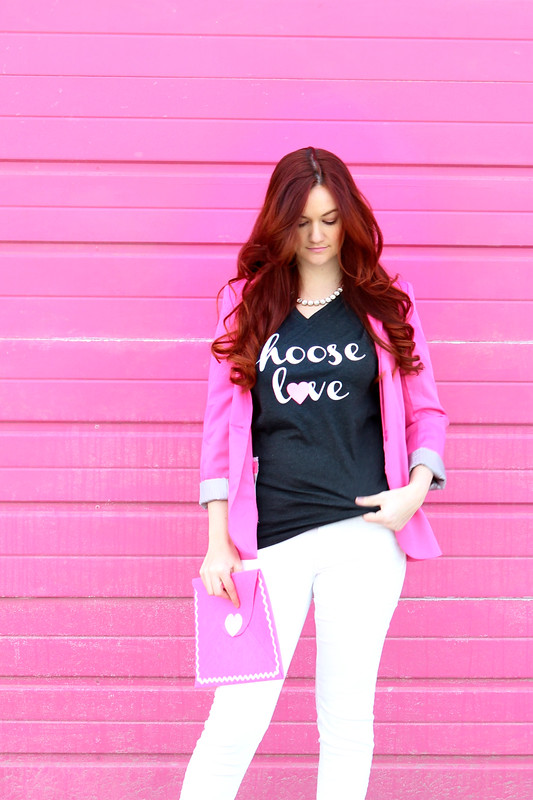 "Chose up of ""choose love"" graphic tshirt in front of the pink wall."