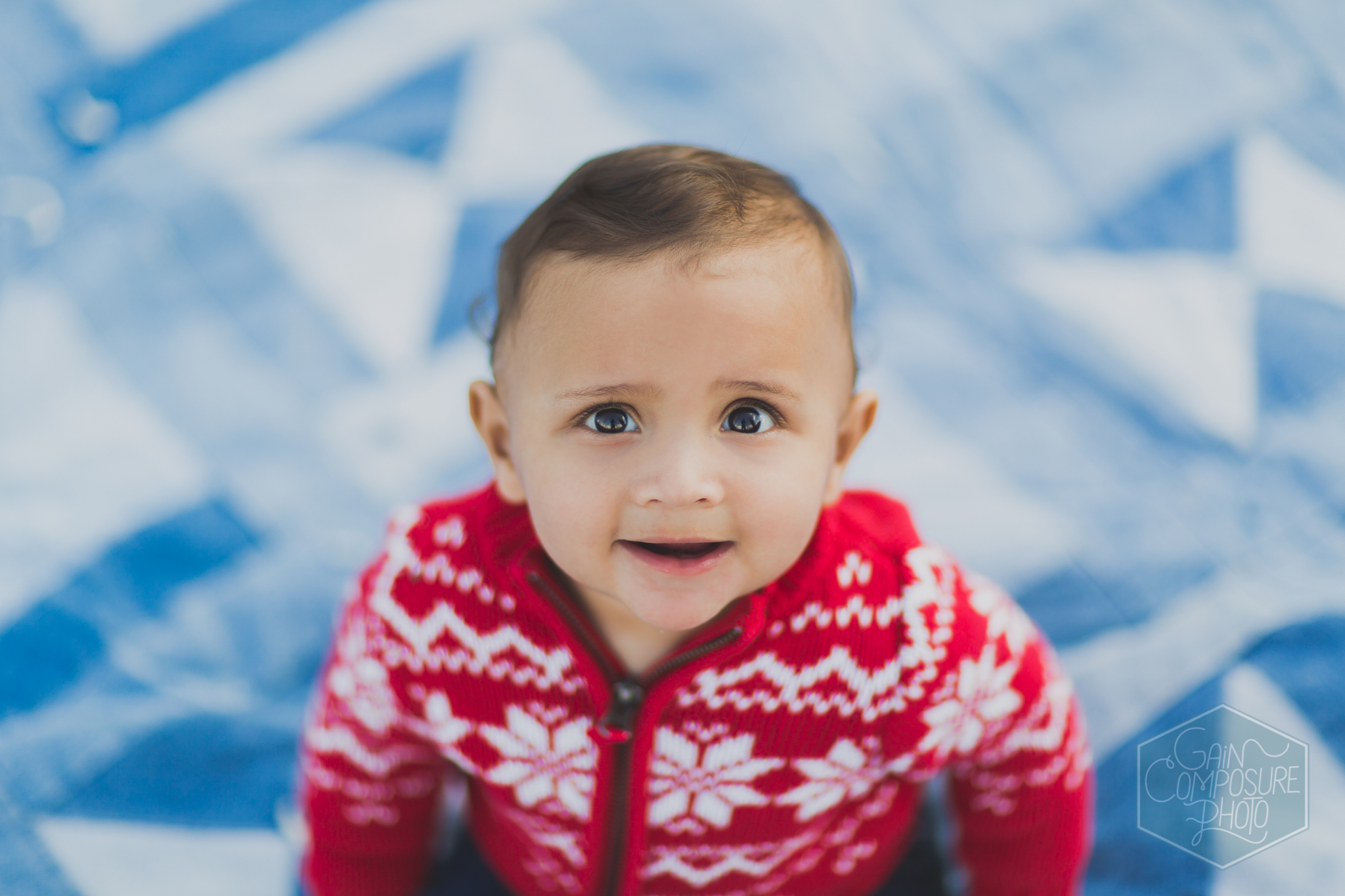 close up of little boy in red sweater on jean quilt