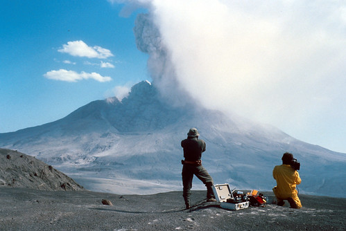 Image shows Mount St. Helens in the near distance from directly to the north, erupting a thick plume of grayish-tan ash. Two geologists stand on the ridge in front of it, filming the eruption. One is kneeling, one is standing. A case of open equipment sits between them.