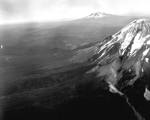 Black and white image shows Mount St. Helens at the extreme right. The most prominent feature is a glacier descending from the summit, and a deep valley it carved almost all the way down the slope in colder times. Looking towards Mount Rainier in the distance, there are several ridges that look like valleys that lava flows once flowed down; the surrounding, softer material has since eroded away. Mount Rainier is visible in the background on the right.