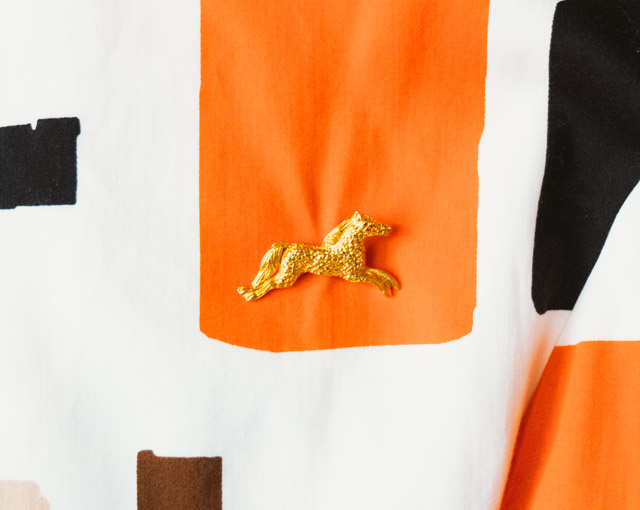 gold horse brooch on retro dress