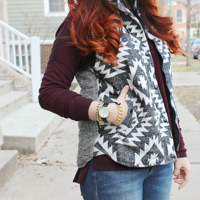 Black and white puffer vest from the side with hand in pocket showing black and gold bracelets from 28four jewelry