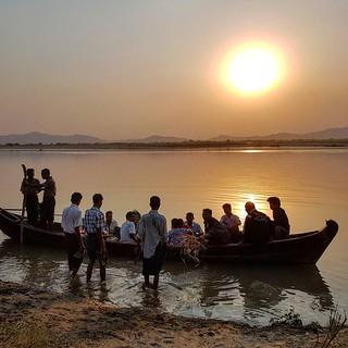 Pessoas a atravessar o rio Rio Irauadi durante o por do Sol em Bagan