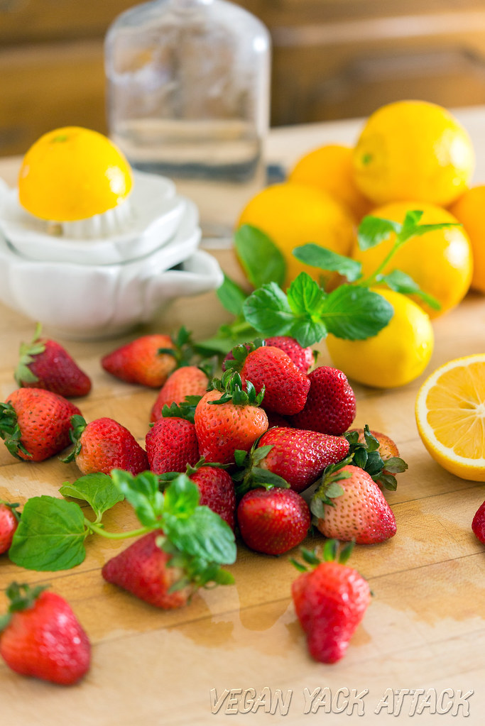 Fresh strawberries, mint, lemons, and a juicer on a cutting board