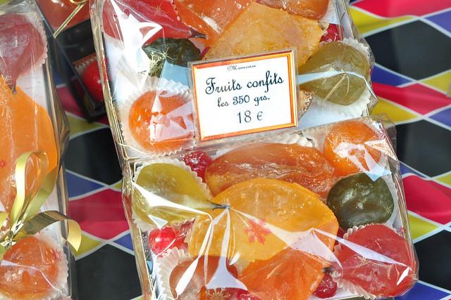 """Die sonnenverwöhnten Regionen Provence und Côte d'Azur bringen zahlreiche wunderschöne, reife Früchte hervor. Kein Wunder also, dass hier auch die traditionelle Confiserie-Kunst des Kandierens und Glasierens zu Hause ist. Wir hatten das Glück, in Nizza zufällig direkt neben der alteingesessenen Pâtisserie/Confiserie """"Henri Auer"""" zu wohnen. Spezialität des Hauses: Fruits confits. Jeden Tag konnte man sich mit einem Blick ins Schaufenster vom Fortgang des zeitintensiven Prozederes des Kandierens und Glasierens in Kenntnis setzen. Jeden Tag werden die in Zuckersirup mehrmals gekochten Früchte akribisch gedreht und gewendet, mit dickflüssigem Sirup übergossen. Bis die Sonnenfrüchte ganz fertig und appetilich glänzend sind und sich Duft und Farbe vollständig entwickelt haben, dauert es allerdings viele Wochen. Mit ein Grund, warum diese handgefertigten Köstlichkeiten einem nicht preiswert nachgeworfen werden. Es sind hübsch anzuschauende kleine Kostbarkeiten, mit denen fabrikmäßig hergestellte Ware nicht konkurrieren kann. Süße Handwerkskunst aus dem Atelier des Confisseurs. Meine Fotosammlung zum Thema Herstellung und Präsentation der """"Fruits confits"""" - Foto Brigitte Stolle März 2016"""