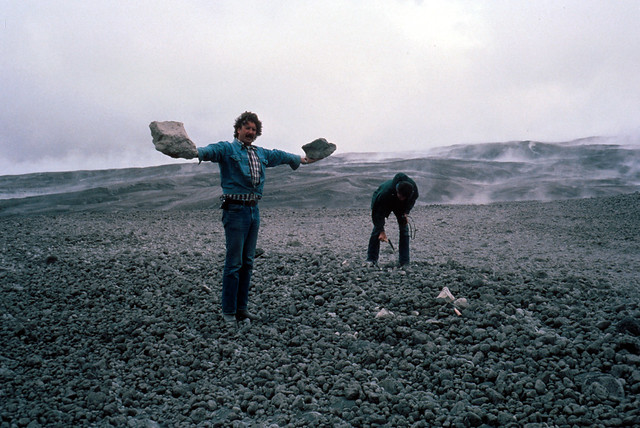 Image shows a couple of geologists investigating the pumice plain. The one in the foreground is standing with his arms held out parallel to the ground, holding two huge chunks of pumice in either hand. He is wearing blue jeans and a plaid shirt with a denim shirt tied at the waist over it. The man behind him is dressed all in dark colors and is bent over putting a temperature probe into the deposits.