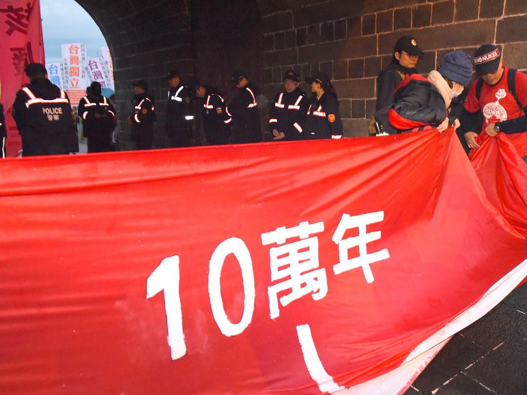 台北場遊行隊伍約有百餘人舉起寬150公分、長30公尺的「萬年廢核時光布條」,最後抵達遊行終點台北城北門,象徵核廢料的存在時間超過任何一座古蹟。(攝影:宋小海)