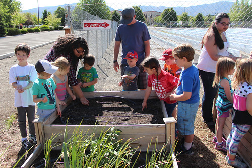 Monique Renteria and Sam Antipa assisting the One World Children's Academy pre-kindergarten class plant seeds