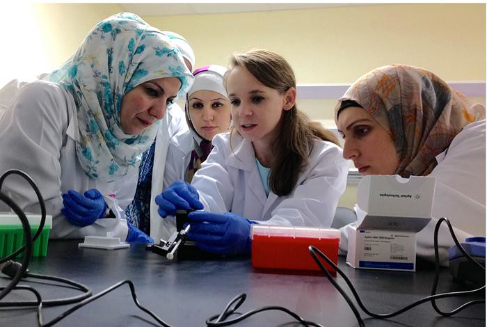 LANL researcher Cheryl Gleasner, center, demonstrates sample preparation and quality control techniques at the newly established Jordan University of Science and Technology Genomics Training Center.