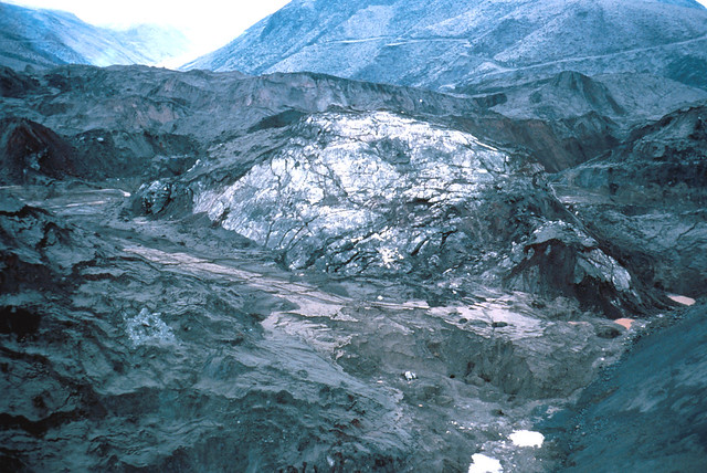 Image shows an enormous dome of ice half-buried in debris avalanche deposits. It's cracked and dusted with gray ash. Beyond it, a ridge shorn of trees rises, a logging road winding along it.
