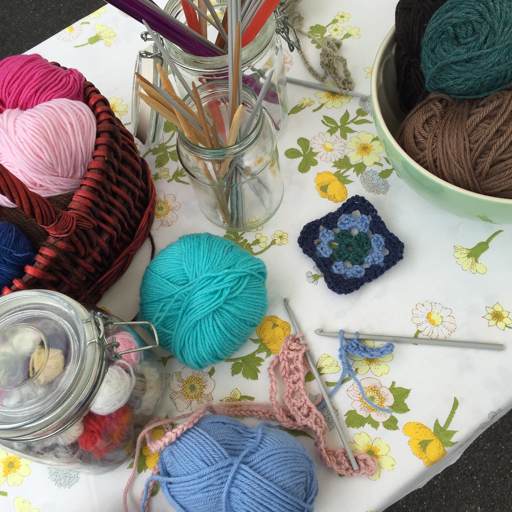 needles and hooks in jars set up on a vintage sheet table cloth. a few bits and pieces of crochet from my 'students'